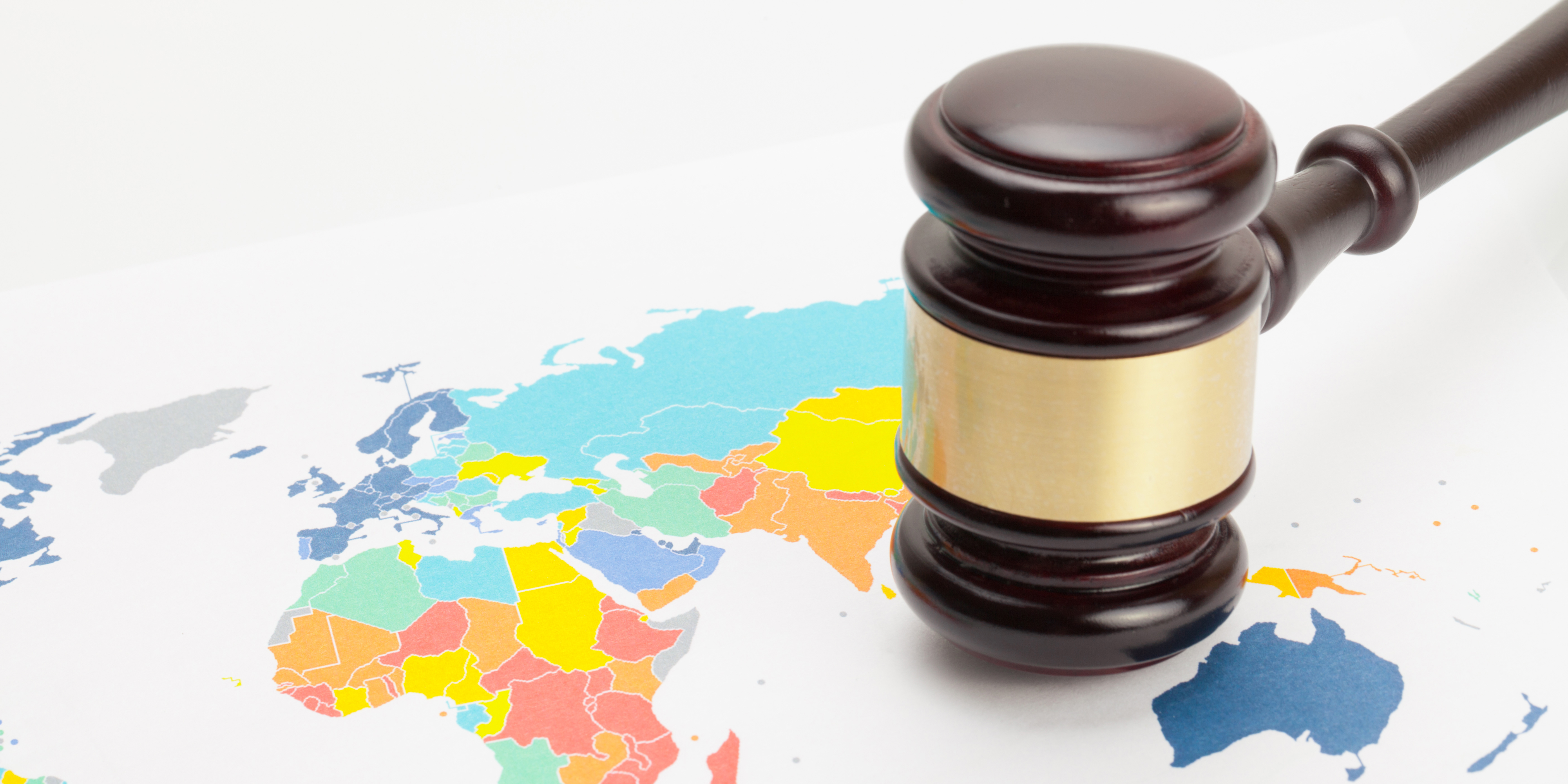 Judge's gavel over colorful world map